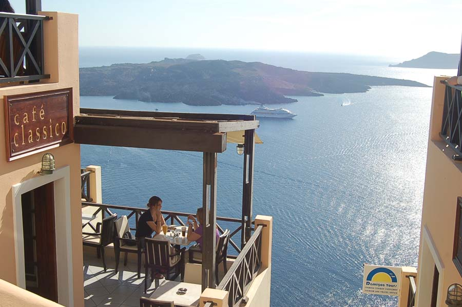 The island of Santorini was once a volcanic cone whose top was blown off, and then became a caldera. From Santorini, you can see several nearby dark volcanic islands, such as those pictured here. As you can see, the cafes on Santorini have breathtaking views.